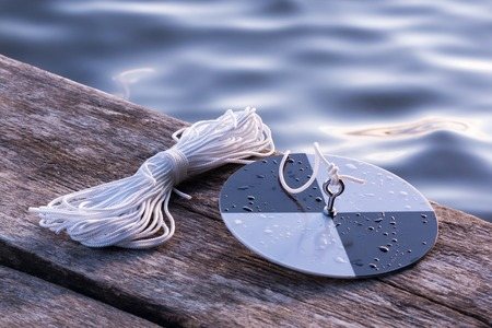 depth measurement: Secchi disk with rope prepared for water transparency measurement.