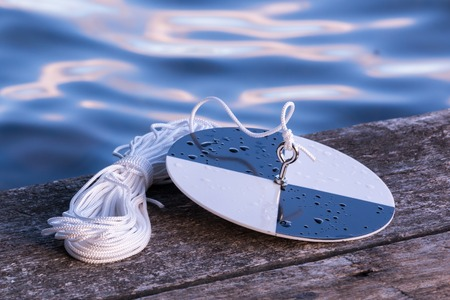 depth measurement: Secchi disk with rope on a wooden dock, prepared for water transparency measurement. Stock Photo