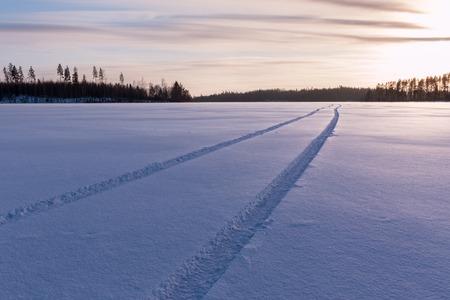 huellas de llantas: neumático de coche rastrea en la cubierta de nieve en un lago