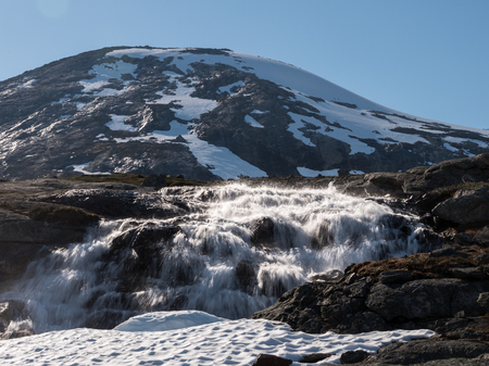 River of melting snow running down from mountain Stock Photo