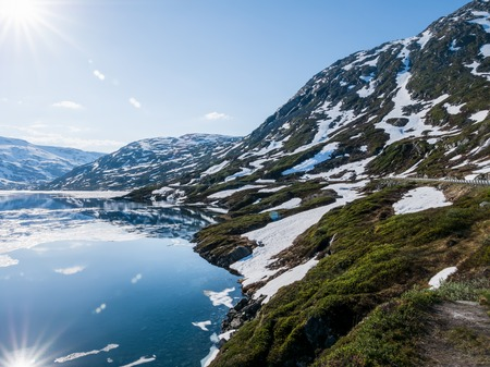 Snow melting by mountain lake