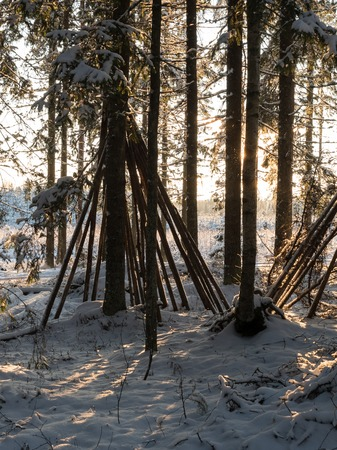 Wooden frame of cone-shaped tent in snowy forest