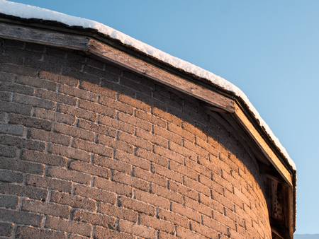 Snowy roof over curved brick wall with light gradient