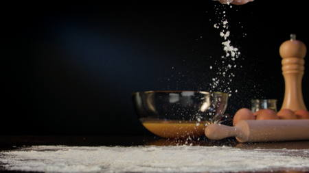 Female hand spilling flour on the table against a dark blue background. Close-up shot