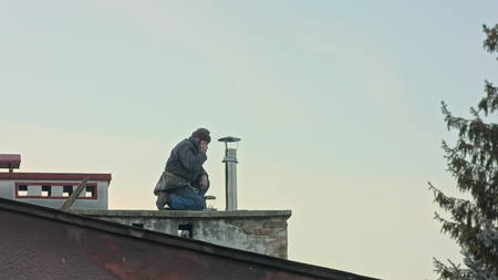 man working on the roof with mobile phone