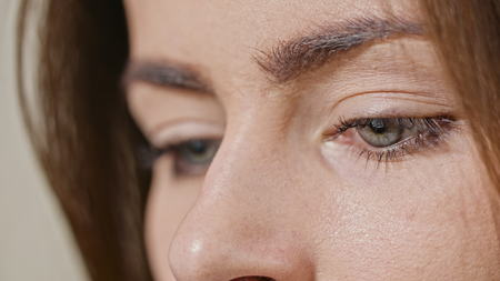 Close up of girls eye reading internet, with reflection of screen in her eye Stock Photo