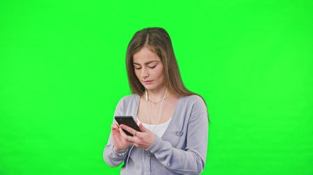 Happy young woman dancing, listening to music on smartphone, A woman is dancing on his own against a green background. Easy to key out and add your own background. Banco de Imagens