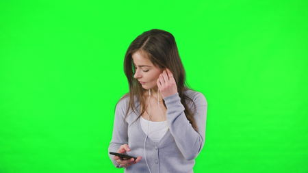 Happy young woman dancing, listening to music on smartphone, A woman is dancing on his own against a green background. Easy to key out and add your own background. Standard-Bild