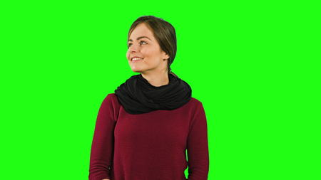 A young modest lady smiling, squinting her eyes and looking down against a green background. Medium shot