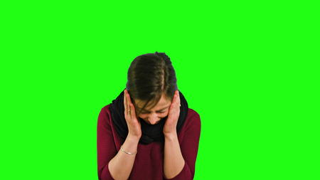 A young lady shaking her head in fury and crying against a green background. Medium shot