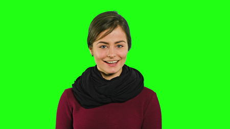 A young modest lady smiling and looking sideways averting her eyes against a green background. Medium shot Stock Photo