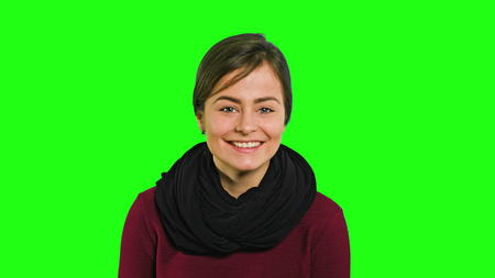 A young modest lady smiling and looking sideways then being disappointed against a green background. Medium shot