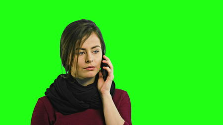 An angry young lady talking on the phone and quarrelling against a green background. Medium shot Imagens