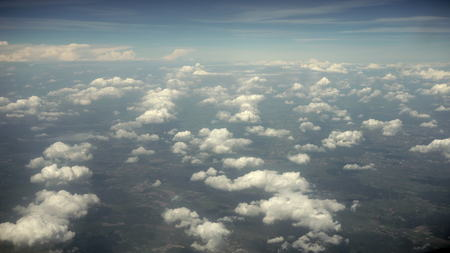 Clouds and earth view from an airplane window. Long shot