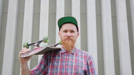 Young readhead hispter with beard and moustaches in jeans and shirt keeps skateboard on the soulder and slowly takes it off, indifferent. Outdoor. Cloudy. Medium. Stabilised. Portrait Foto de archivo