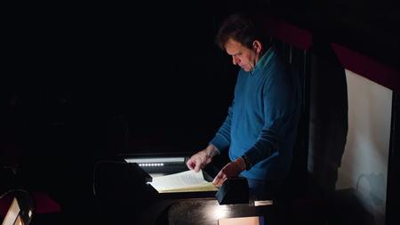 Lviv, Ukraine - June, 2017: Mid aged conductor alone in dark orchestra pit studies sheet music and tweets the tune. Indoor. Medium