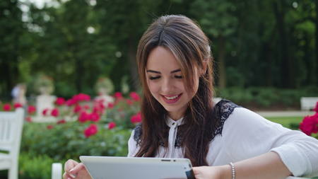 Beautiful brunnette lady sitting on a white bench in the park and using a tablet. Medium shot Stock Photo