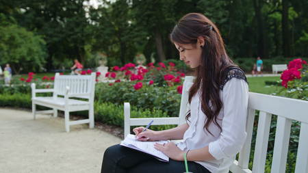 Beautiful brunnette lady sitting on a white bench in the park and writing. Medium shot