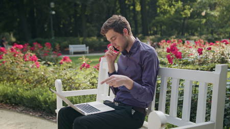 A young man sitting on a white bench in the park and using a laptop and talking on the phone. Medium shot
