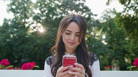 Beautiful brunnette lady sitting on a white bench in the park and using a phone. Close-up shot Stock Photo
