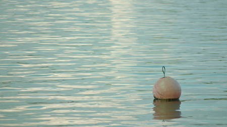 A buoy floating on the surface of the water. Long shot