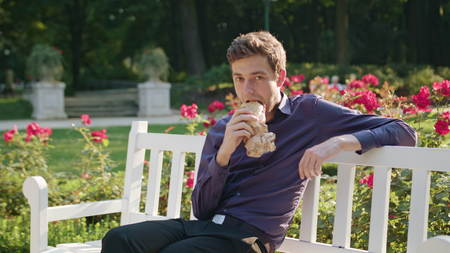 A young man sitting on a white bench in the park and having a snack. Medium shot