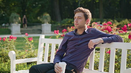 A young man sitting on a white bench in the park and having a coffee. Medium shot