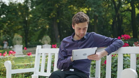 A young man sitting on a white bench in the park and using a tablet. Medium shot