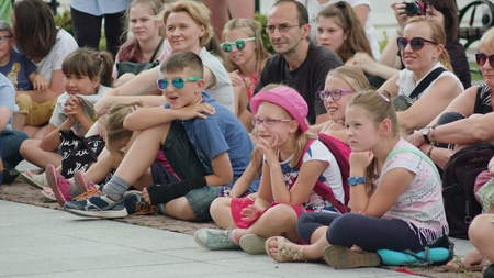 Lublin, Poland - July 2017: Kids and adults are laughing while watching street performance within Festival Sztukmistrzow sitting on the paving tile down the street. Sunny. Outdoor. Medium. Editorial