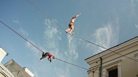 Lublin, Poland - July 2017: Slackliners in old town at Urban Highline Festival placed in old city space. Two slackliners in frame: one is moving, and the other is laying on the slackline. Sunny. Medium. Stabilized Editorial