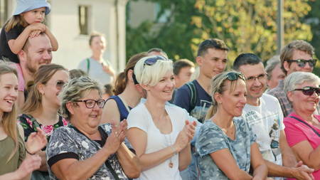 Lublin, Poland - July 2017: Kids and adults are laughing and claping while watching street performance of Claudio Mutazzi within Festival Sztukmistrzow staying and sitting on the paving tile down the street. Sunny. Outdoor. Medium. Stabilized
