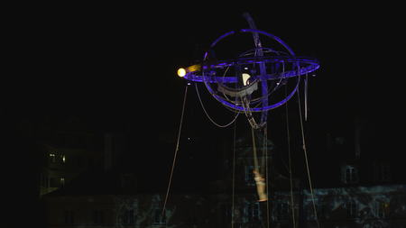 Lublin, Poland - July 2017: Deus Ex Machina performs Galileo on Zamkowy Square during Festival Sztukmistrzow. Acrobats swaying on the rope attrached to the spherical construction. and dancing. Outdoors. Medium. Night. Stabilized. Editorial