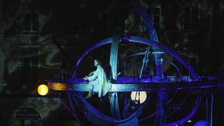 Lublin, Poland - July 2017: Deus Ex Machina performs Galileo on Zamkowy Square during Festival Sztukmistrzow. Spherical construction hanged in the centre, acrobats on it. Outdoors. Close up. Night. Stabilized.