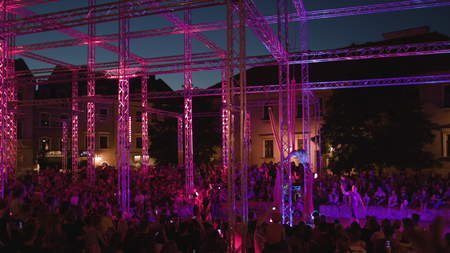 Lublin, Poland - July 2017: Silk Siisters aerial acrobatic show at night on Po Farze Square during Festiwal Sztukmistrzow. Crowd watches the show. Outdoors. Night. Dark. Wide angle. Camera from above. Stabilized