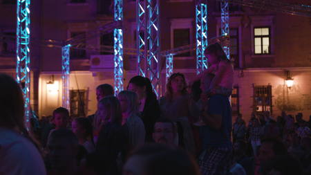Lublin, Poland - July 2017: Silk Siisters aerial acrobatic show at night on Po Farze Square during Festiwal Sztukmistrzow. Crowd watches the show. Kids are sitting on the parents shoulders. People on the first plan are sligthly blurred. Outdoors. Night. D