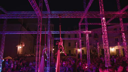 Lublin, Poland - July 2017: Silk Siisters aerial acrobatic show at night on Po Farze Square during Festiwal Sztukmistrzow. Crowd watches the show. Outdoors. Night. Dark. Medium. Stabilized