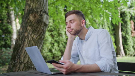 A young man using a phone in the park and sitting at the table. Medium shot. Soft Focus Stock Photo