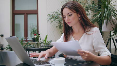 A beautiful girl using her laptop and verifying data with a sheet of paper in the room. Medium shot. Soft focus.