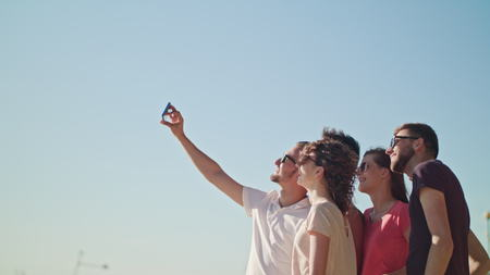 Young people making a selfie on the beach. Medium shot. Soft Focus.