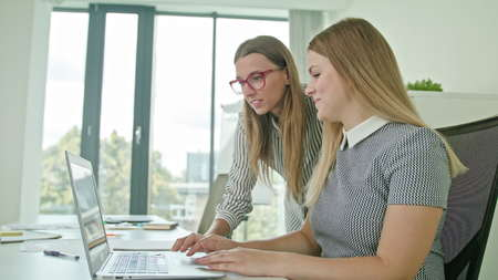 Two woman in modern start up office female team leader pointing at screen discussing diverse people group teamwork using laptop display