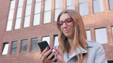 A young beautiful lady using a smartphone near the brick building. Close-up shot.