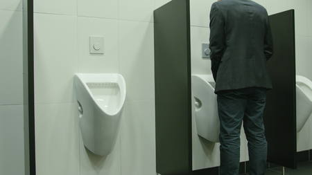Man peeing to toilet bowl in restroom. Long shot Archivio Fotografico