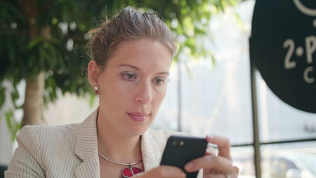 A young beautiful lady using a smartphone in the cafe. Close-up shot. Soft focus.