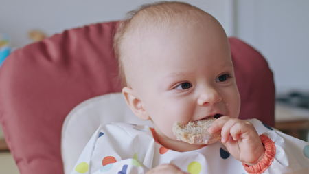 A baby girl eating bread at home. Close-up shot. Soft focus.