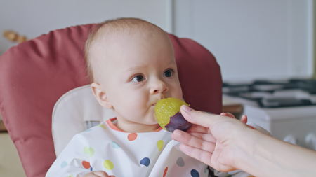 Una niña comiendo una ciruela en casa. Fotografía de cerca. Enfoque suave.