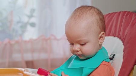 A baby girl eating puree at home. Medium shot. Stock Photo