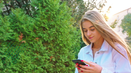 Woman texting on smartphone looking happy outside, Caucasian girl in her 20s happily texting on phone in public place, 4k