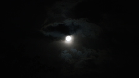 A realtime shot of the moon and clouds in the night sky.