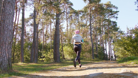 A young y with pink hair jogging in the forest. Long shot Stock Photo