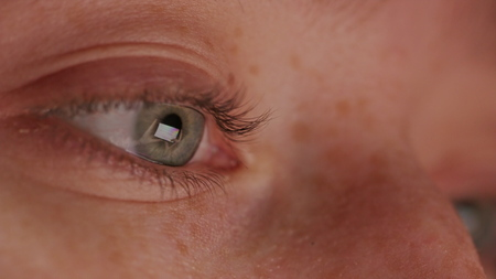 close up macro eye screen reflecting on iris browsing online social media at night